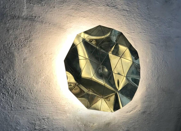 The Brass Hotplate wall sconce, is a contemporary faceted solid brass sconce, with LED lit Malagasar bone polymer diffuser behind the folating plate     Materials: Brass, Malagasar bone polymer. Dimensions: 240mm ø x 30mm deep Light source: 24volt