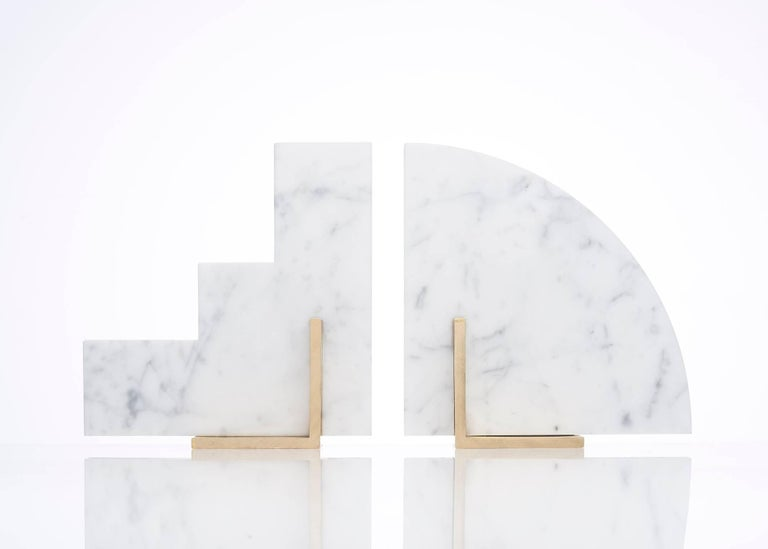 Meet Curvy and Steppy; the two individual bookends which as a pair are known as The Odd Couple Bookends. Here shown in a honed Italian Carrara marble and a brushed brass base. The marble cut into two geometric shapes and balanced over a brass