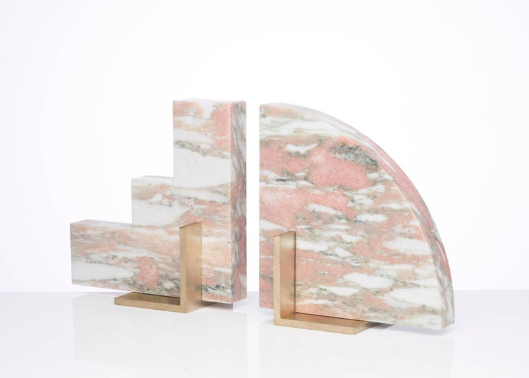 Meet Curvy and Steppy; the two individual bookends which as a pair are known as The Odd Couple Bookends. Here shown in a honed Norwegian Rose marble with a brushed brass base. The marble is cut into two geometric shapes and balanced over a brass