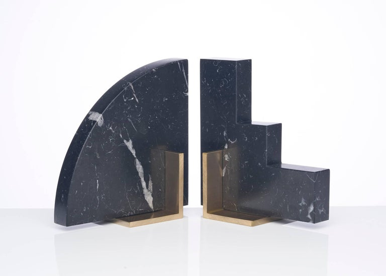 Meet curvy and steppy; the two individual bookends which as a pair are known as the odd couple bookends.  Here shown in a honed Nero Marquinia marble and a brushed brass base. Nero Marquinia marble from Spain is cut into two geometric shapes and