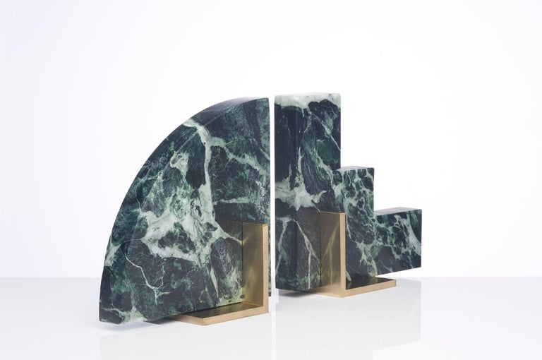 Meet Curvy and Steppy; the two individual bookends which as a pair are known as The Odd Couple Bookends. Here shown in a honed green marble and a brushed brass base. The marble is cut into two geometric shapes and balanced over a brass angle. The