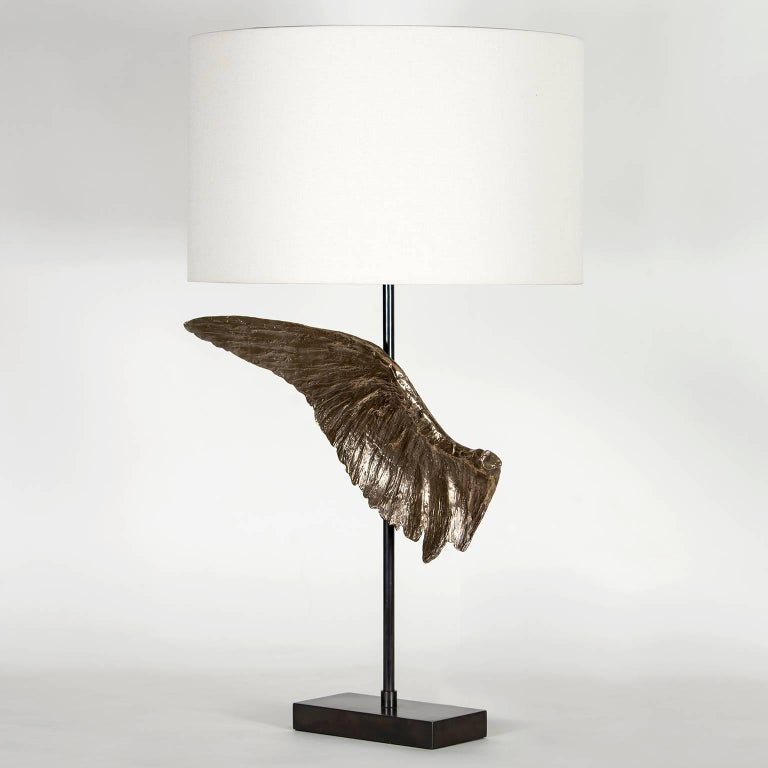 The Voltaire table lamp consists of a cast bronze wing sculpture inspired by the past and present using age old and modern techniques to create each piece. There is a left and right wing available and each has its unique details and slight