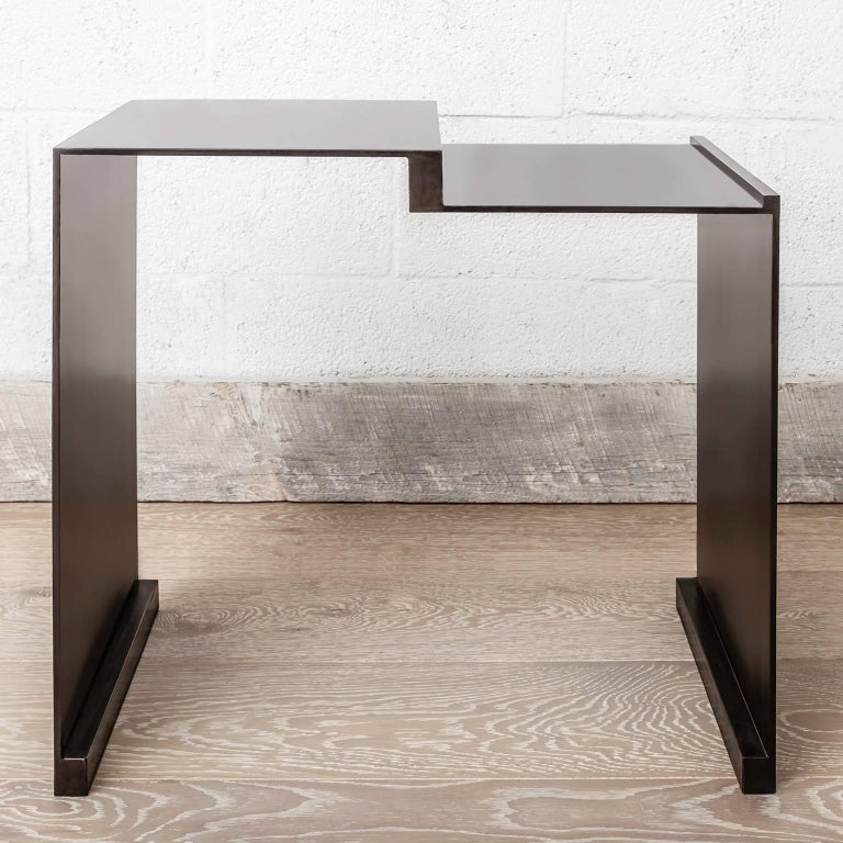 The Roque side table evokes a warm modern elegance with simple lines and solid materials. The main structure is composed of blackened steel in various dimensions and segments that create a minimalistic sculptural form. It is offered with or without