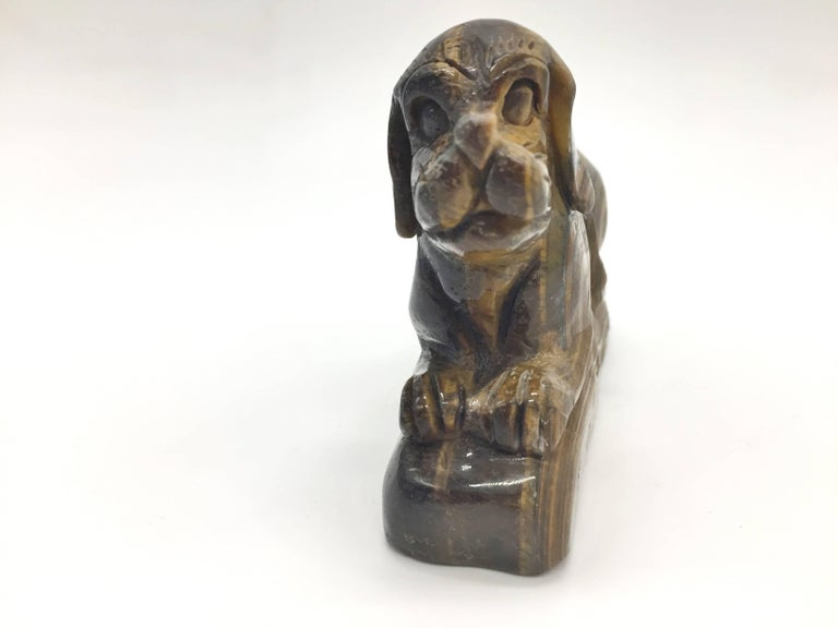 Adorable dog is carved from a block of all natural tiger's eye. The iridescence that is unique to this gem stone enhance the charm and beauty of the piece. Tiger's eye is a member of the quartz group of chalcedonies. It has the power to enable clear