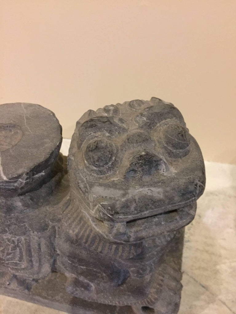 Wonderful pair of foo dogs is hand-carved out of solid stone. Details of lotus flowers can be observed on their saddles. A candle feature makes them unique candle holders. Foo dogs are guardians whom the Chinese believe to protect the house and its