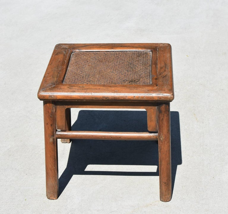 A 19th century Chinese stool. It has all the rustic charm of country and the nice lines of Ming furniture. The top is constructed with a floating panel with a rattan seat inset, a typical southern make. Round legs soften the lines and add elegance.