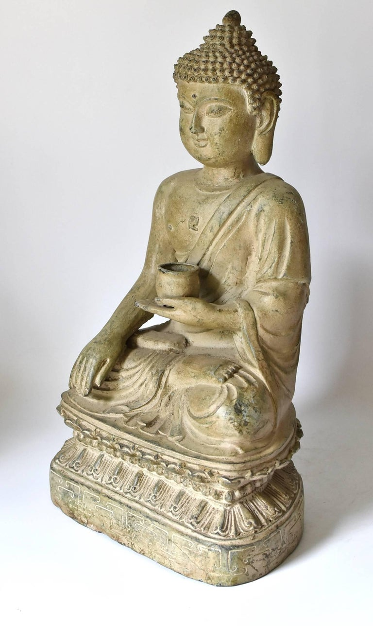A beautiful pale green bronze sitting Buddha statue. The style of the piece is of the Tang dynasty era, with a full face, long ear lobes and scrolled hair style. Beautiful, finely defined facial features convey a sense of calm and serenity. Buddha