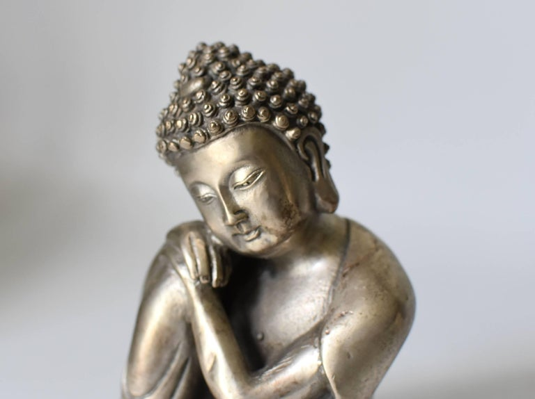 A beautiful silvered brass metal contemplative Buddha. This is a rare version of Buddha depiction, in an unique style. Through fine craftsmanship, the statue conveys a sense of peace and calm. This piece is small and exquisite, perfect as a desk top