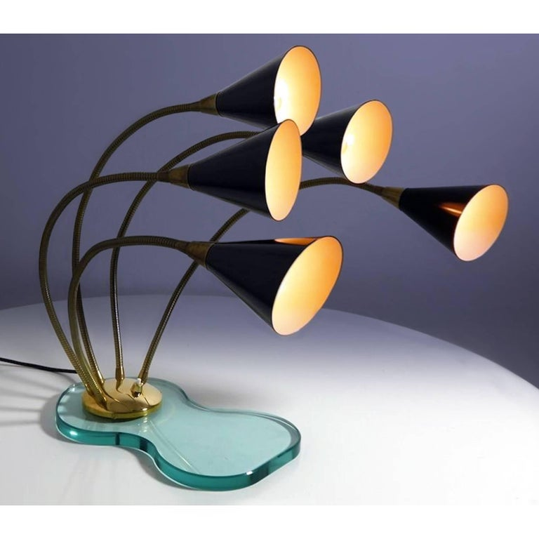 Amazing large table lamp five lights in Stilnovo style, finished with enameled black metal shades mounted on gooseneck brass arms and fixed on a beveled thick glass base. It's a very stylish lamp with a unique design, offering adjustable infinite