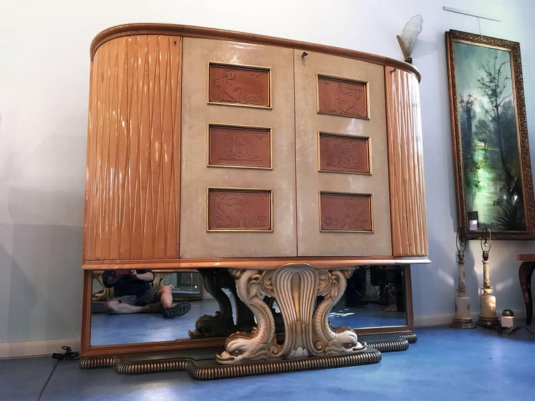 Spectacular wet bar cabinet in maple and parchment design attributed to Osvaldo Borsani in the 1940s. On the parchment doors there are wood sculptured figures of stylized women, luxury insides in maple that light up when opening the doors, glass top