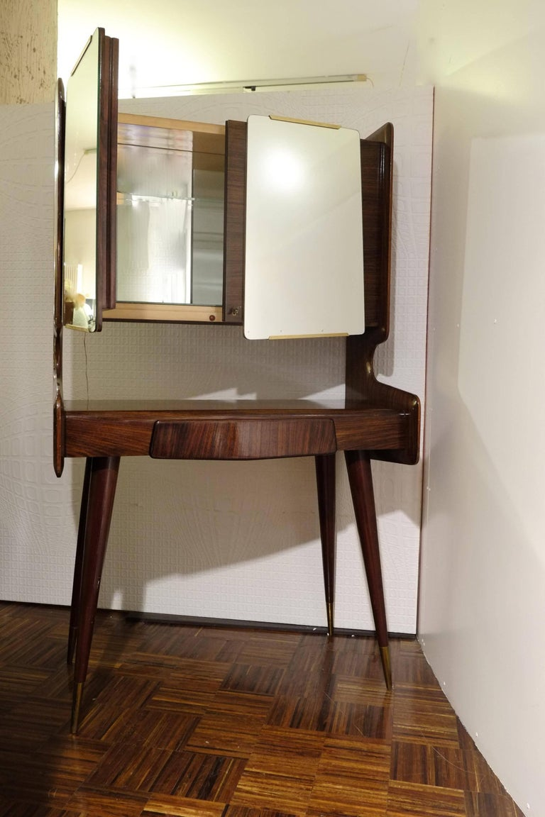 Tall standing dry bar cabinet in the style of Ico Parisi. Cabinet stands on thin, brass capped legs. Beautiful veneer work over the expressive lines of the main case. Cabinet has main surface with one central drawer below and mirrored double doors