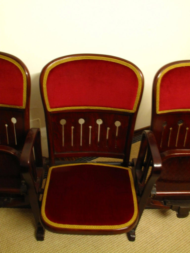 Original set of four connected bentwood theatre chairs by Thonet, circa 1907. Each chair folds up and down, has velvet-covered padding to the seat and back, as well as decorative piercing to seat lower back.