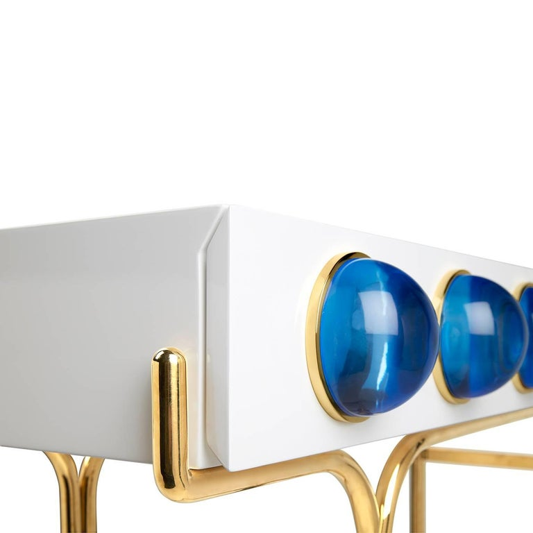 A glossy, white lacquer cabinet cradled by a sinuous brass framework and capped with blue solid Lucite cabochons. Small footprint but big impact, our Globo console is guaranteed to deliver mega glamour.