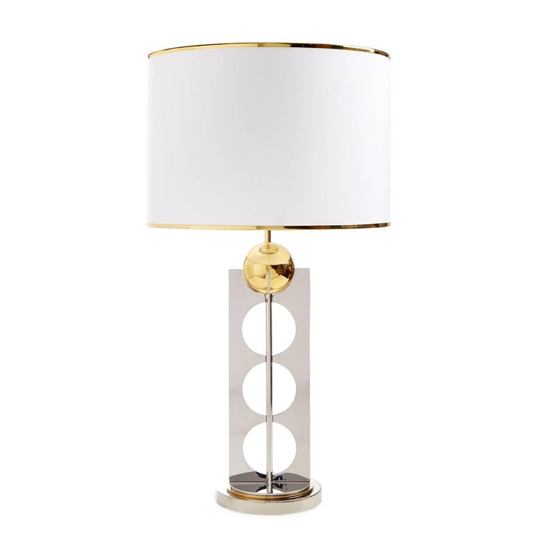 Elemental elegance. An exploration of mixed metals, Wiener Werkstatte austerity, and futuristic glamour. A steel x-base with mod circle cutouts supports a brass sphere fixture. Brass banding on the shade adds an extra layer of Machine Age modernism.