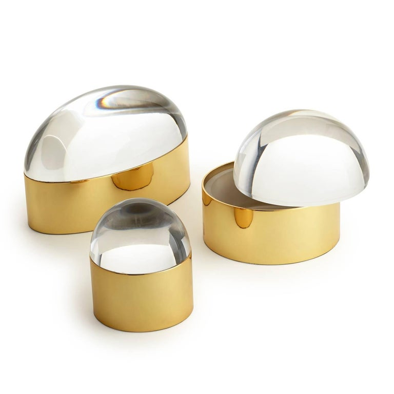 Futuristic elegance. Our globo boxes are an intriguing addition to any tabletop, powder room, or cocktail table. The polished brass base lined in turquoise velvet complements a gem-esque Lucite lid. Sold as a set including three sizes. Contact