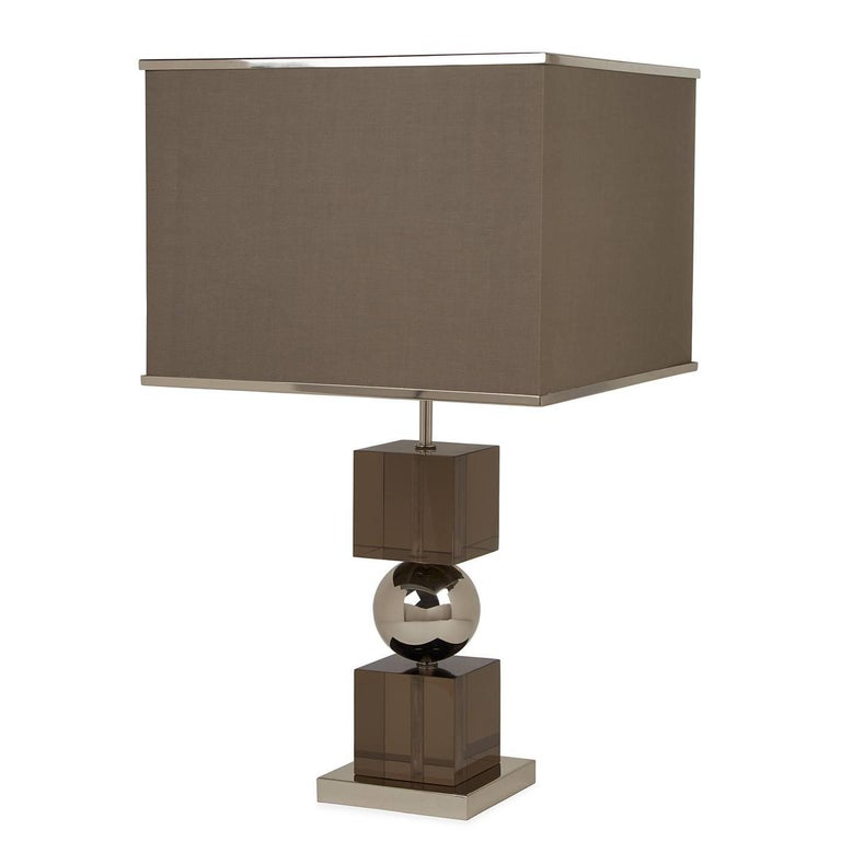 Clearly cool. Traditional elegance meets modern glamour in our Jacques stacked table lamp. Moody smoked Lucite cubes sandwich a stainless steel ball for gravity-defying glamour. A polished nickel trim gives a jewelry-like finish to the square fabric
