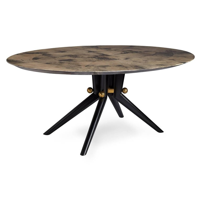 Lacquered vellum. A sculptural splayed leg base with brass spheres supports an oval top in high-gloss lacquered charcoal vellum. With a dash of Wiener Werkstätte formality and a soupçon of groovy Italian modernism, our Trocadero Table adds a