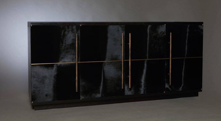 The RAVEN Credenza celebrates the beauty of unpredictable occurrences in natural materials, combined with the artist's tailored perspective. This all-leather clad piece was built to sit in a regal setting, with its black hair calf doors and forged