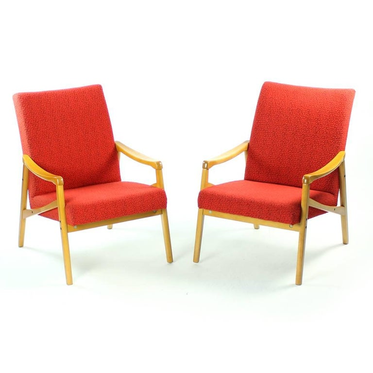 These two beautiful armchairs show the typical Mid-Century armchair design by Interier Praha. They were created in 1971 in Czechoslovakia. Upholstered in original red fabric which shows only minor wear. The lighter wood in very good condition and