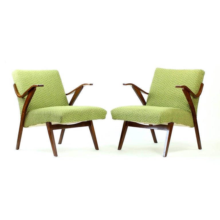 These beautiful armchairs are a Classic of Czechoslovakian design. Produced in 1964 by Mier furniture company, they are in original condition. Original green upholstery shows some fading but is still in very good condition. The dark beech wood is in