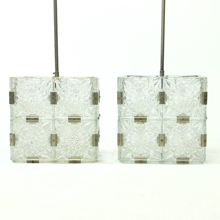 These are two beautiful glass pendants produced by Kamenický Šenov in 1970s. The light is hanging on a chrome metal construction. The light is made of square glass panels combined to make a glass cube. Beautiful design and light. Each panel is