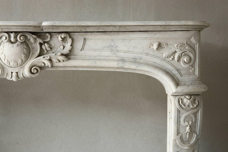 Very rare marble antique fireplace from the era of Louis XIV of white Carrara marble. This unique fireplace dates back to the 19th century. The curved legs are decorated with scallops and cannellures. The front part has a beautiful scallop in the