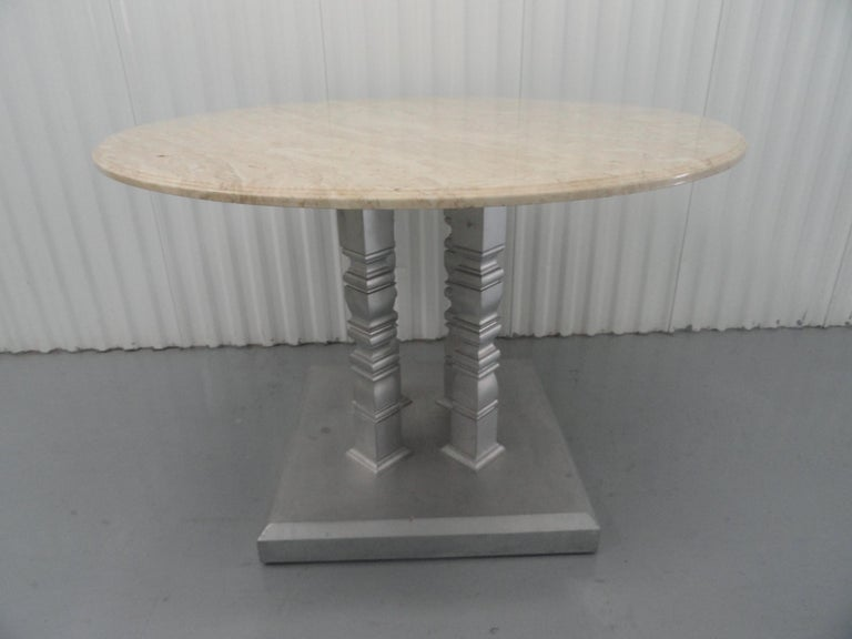 Custom designed table with four-column base, after a design by John Saladino. Custom base with silver finish. Round marble top.