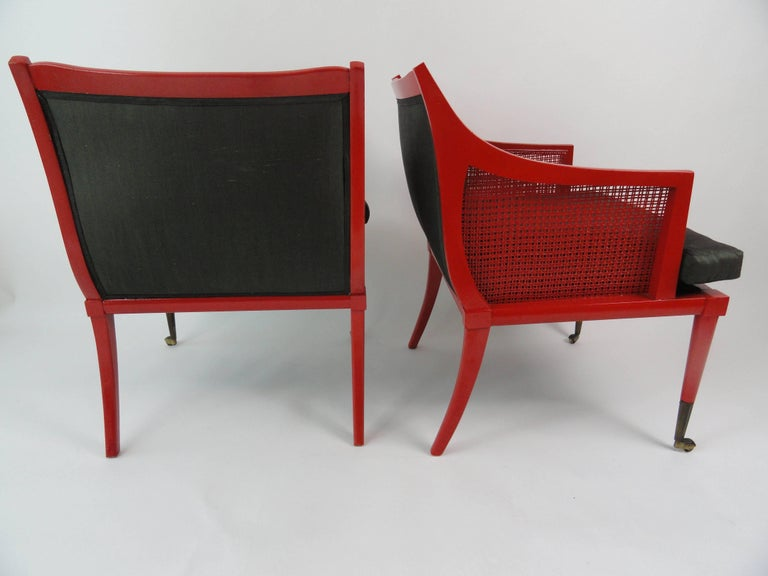 Pair of red lacquer wood chairs, sculptural form with brass sabot, cane sides. Modernist style by Edward Wormley for Dunbar.