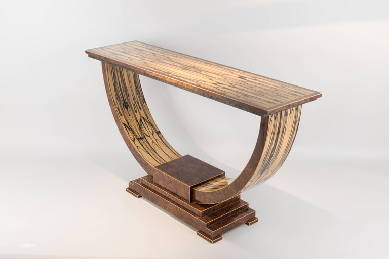 A rare and exquisite veneer, white ebony is used extensively throughout. Beautifully figured, it is paired with fine English walnut. The stone edging incorporating gold thread is produced especially for this table completing this refined console