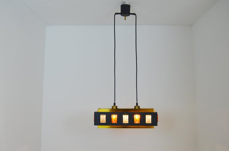 A rare ceiling lamp made from brass, laquered metal and glass. Gives a nice and soft light. The lamp is made by Einar Bäckström and the glass parts is designed by Erik Höglund. Measurents is for just the lamp part. Height is adjustable thanks to