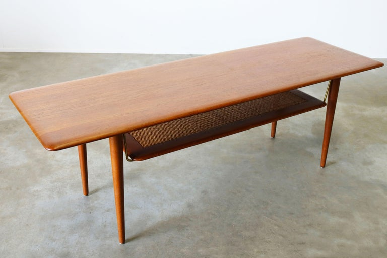Peter Hvidt & Orla Mølgaard Nielsen coffee table FD 516 designed in 1956 and manufactured by France & Son in Denmark. High-end coffee table made of teak, with shelf brass rods and teak frame and woven cane inlay. The beautiful brass supporting rods