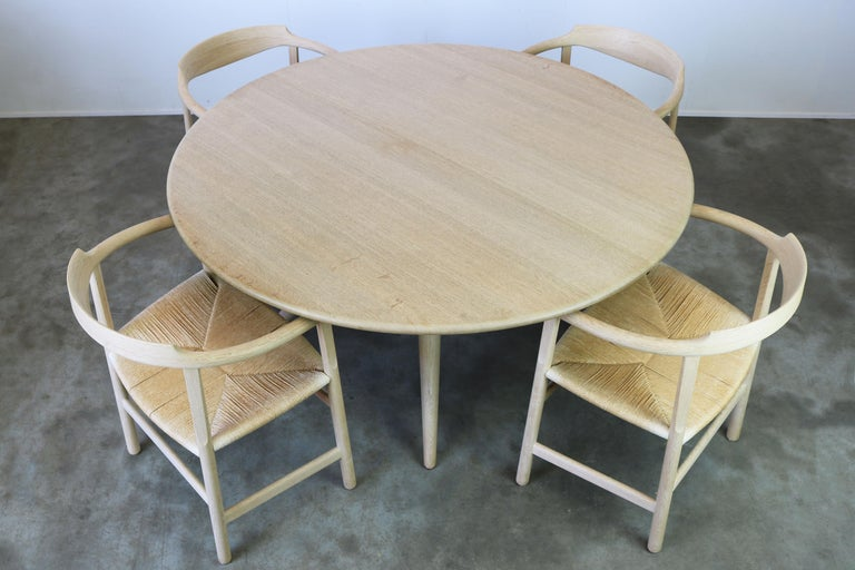 Magnificent Danish dining room set in soaped oak designed by Hans J. Wegner for PP Mobler in 1982. The set is fully original and consists of four soaped oak papercord arm chairs Model: PP205 these are no longer in production and very rare and a