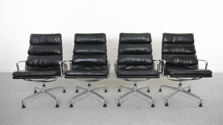 Vintage set of four easy chairs EA 216 soft pad. Manufactured by Herman Miller / Fehlbaum, Germany. Original black leather upholstery. Embossed Herman Miller Logo. One chair has a rest-label of the early Miller Logo. These swivel-chairs are very