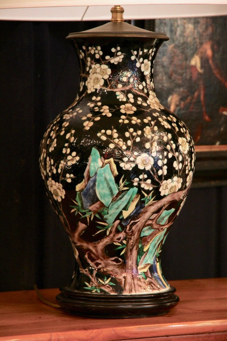 Baluster shaped ceramic vase of the black family sealed on a wooden base (invisible mark). The lip of the vase is set in a bronze element that supports the stem of the bulb.  The vase is decorated on all sides with white prunus flowers on a