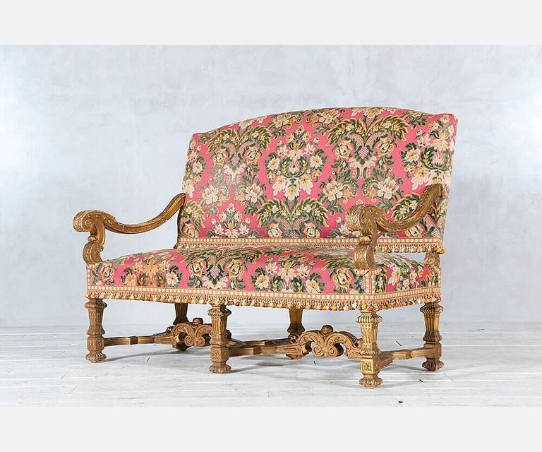 Gorgeous, pair of late 19th century French Baroque-style giltwood settees with finely carved decorations. Gilt finish is naturally distressed. The settees have been recently reupholstered in a floral patterned cut velvet and finished with a tassel