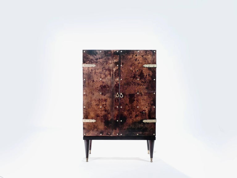 Italian designer Aldo Tura was known for creating decorative pieces that often incorporated goatskin parchment, which creates the lovely dappled, tortoise-shell-like look seen here on this bar cabinet. The varnished goatskin parchment surface, in