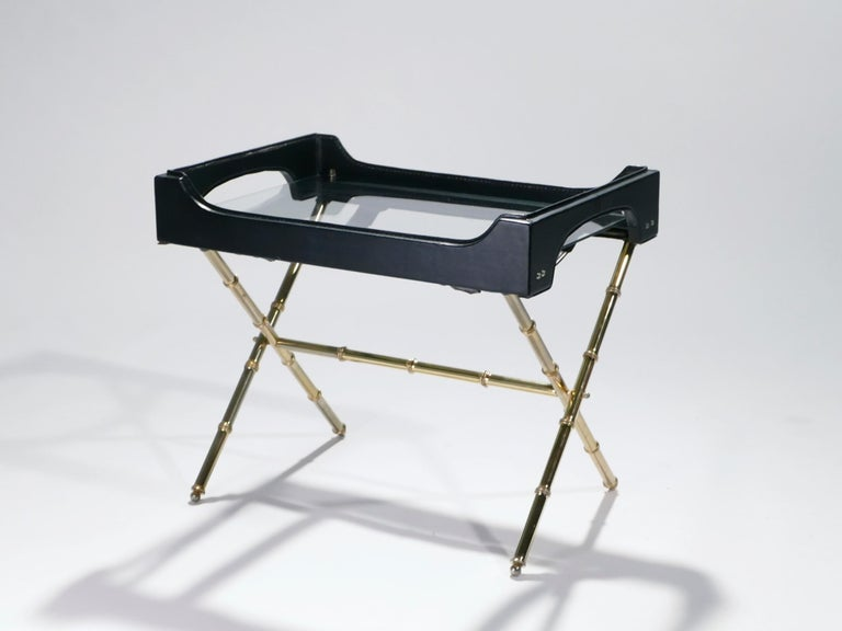 Golden brass and masculine black leather are stunning together in this table by French Art Deco modernist designer Jacques Adnet. The brass structure forms a crossing stand meant to support the accompanying leather tray, which can be removed when