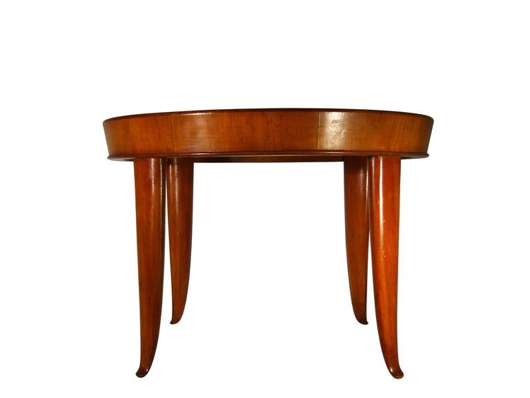 This elegant coffee table was produced in Italy in the 1940s and it is attributed to Guglielmo Ulrich, as it resembles other very models closely. It is made from a wooden structure with a round glass top. The table has been partially restored and