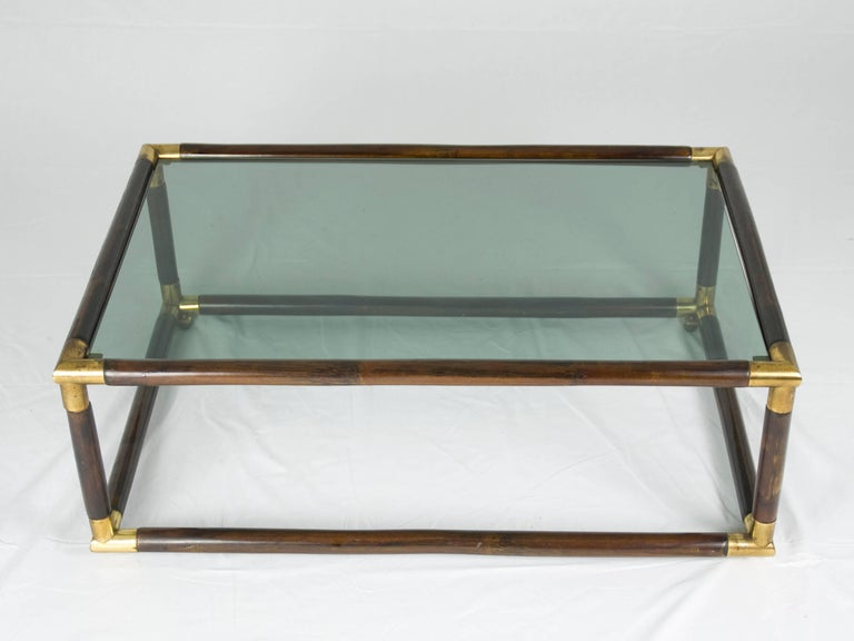 This elegant coffee table was produced in Italy around the 1970s. It is made from a laquered bamboo structure with brass junctions and features one smoked glass shelf. The table remains in excellent vintage condition: a small chip on the edge of