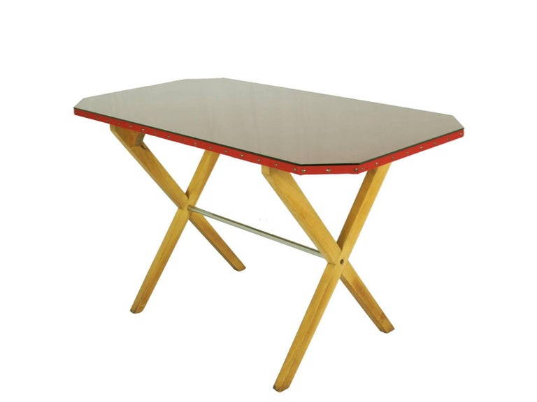 A beautiful and rare desk in the style of Franco Albini. It is made from a wooden crossed structure with a chrome-plated rod. A studded octagonal top is covered with red fabric and glass.