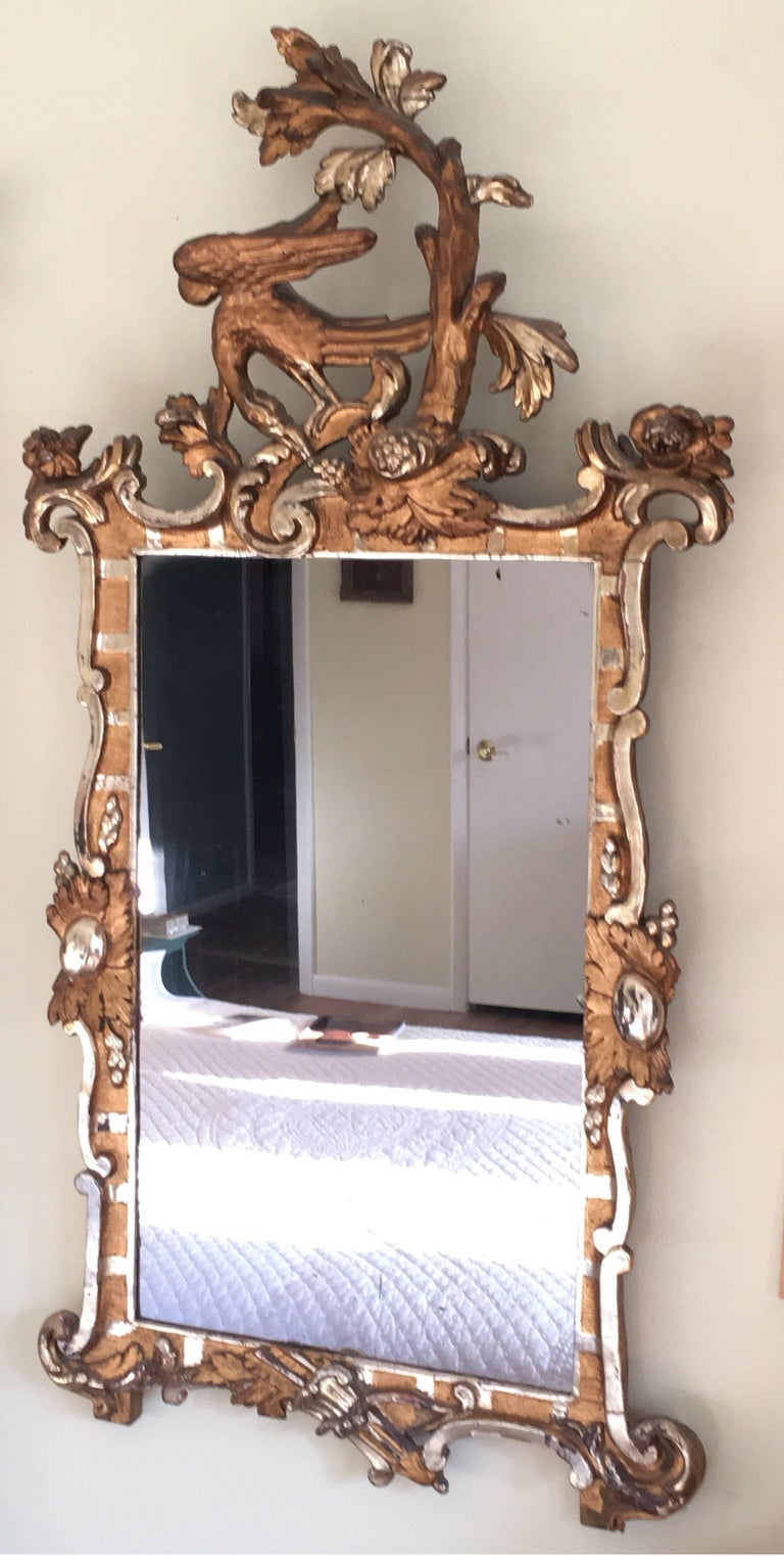 A rare and stunning antique 18th century giltwood and gesso Rococo mirror from Schleswig-Holstein, crested by a graceful Ho Ho bird feeding on a cluster of grapes, flanked by classical mythological motifs of more grapes, golden eggs, and a bow and