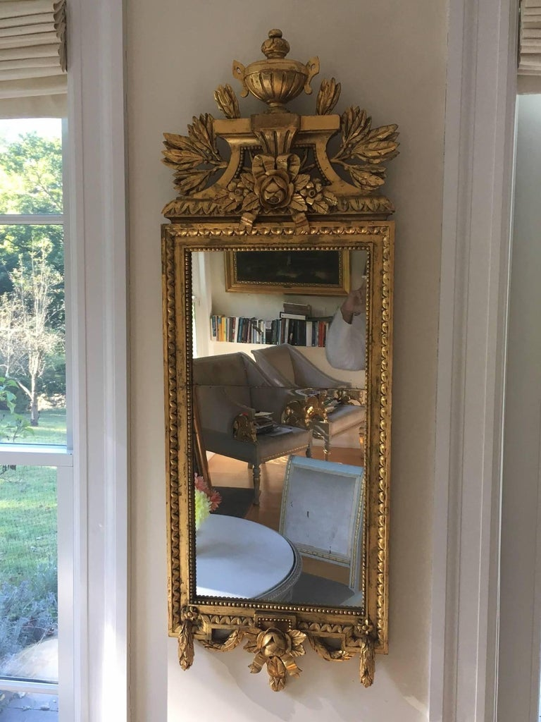 Gorgeous carved giltwood Swedish Gustavian style rectangular wall mirror circa 1880's. Lavishly decorated in the French neoclassic style with leaves, berries, urn, garlands, ribbons and roses. Mirror in two plates.