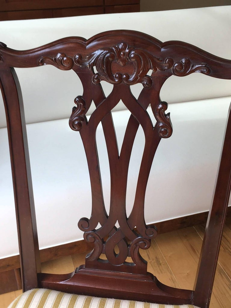 Absolutely charming pair of Danish Chippendale style side chairs, done in mahogany, circa 1870. Carved and pretty floral back splat, foliate knees, claw and ball feet in the front, saber legs in the back.  Very good antique condition, minor