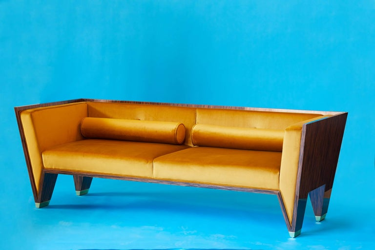 The Wedge Sofa is a timeless handmade Art Deco sofa in a contemporary style. This striking sofa is well built and strong. The velvet is like butter and Macassar Ebony has a high gloss lacquer finish. The feet are made out of solid brass and have a
