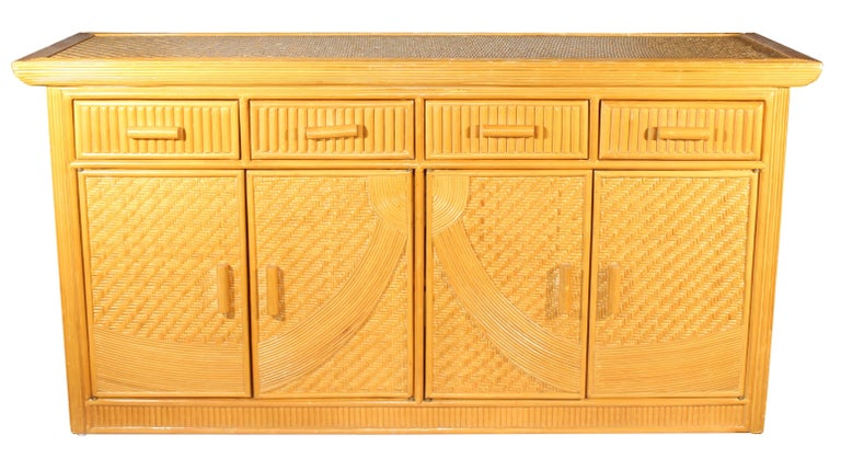 Elegant geometric artdeco weaved bamboo design that extends to the side panels. Four top drawers and four doors which open up to two shelved cabinets.