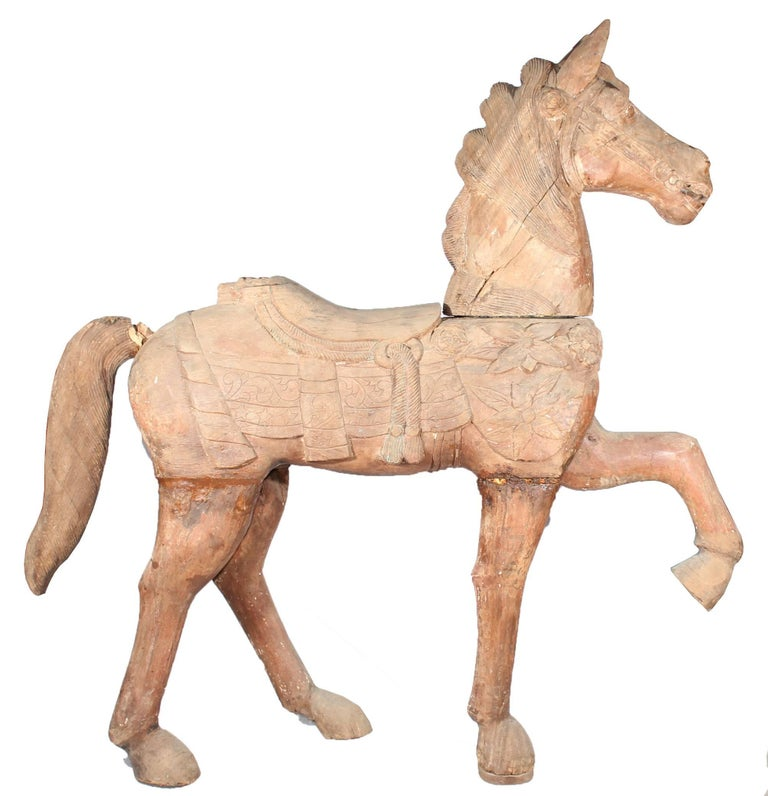 Hand carved wooden trotting horse with remnants of the original painting.