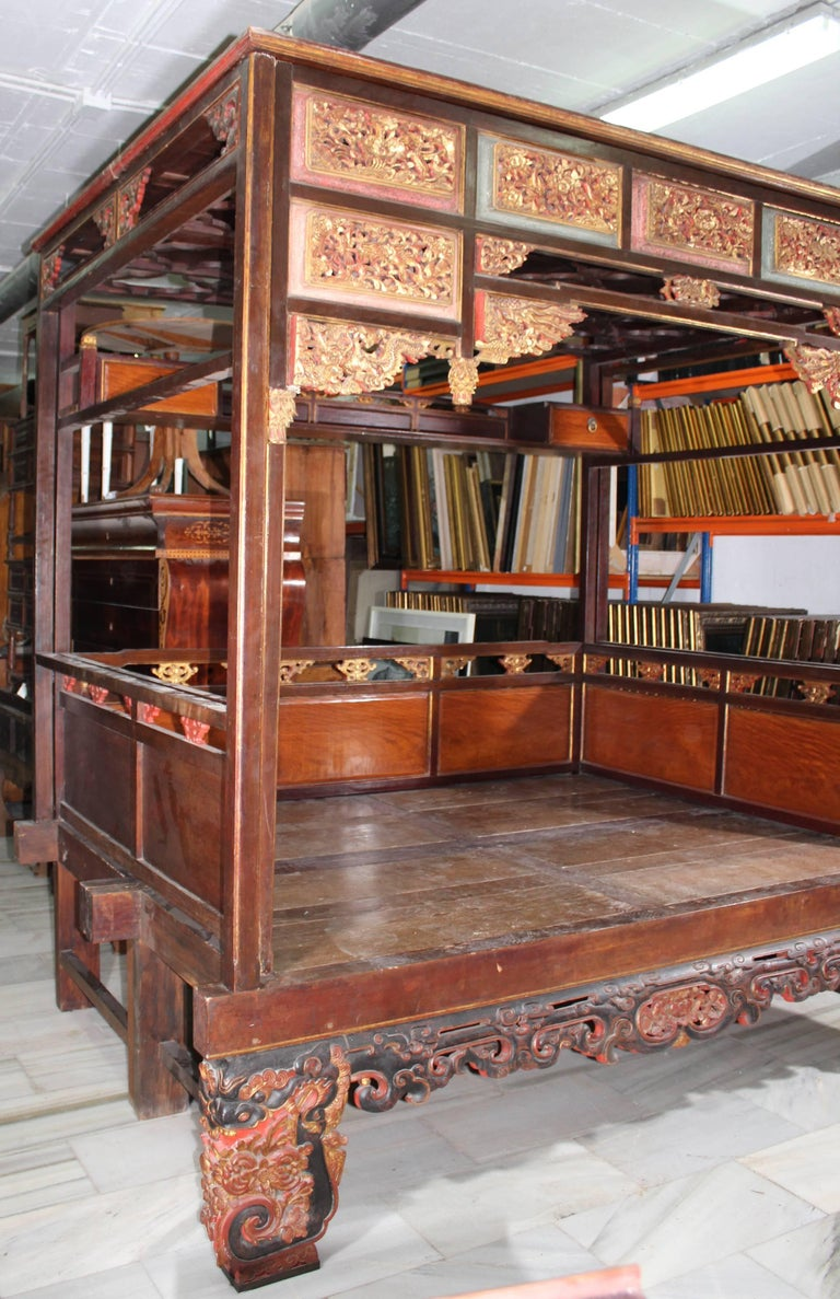 This is a wonderful example of a canopy bed from Shanghai Province, China. Made of Chinese Northern Elm, this bed features hoofed feet and multiple floral carvings.   The exterior is heavily decorated with gold leafing, carvings, ornate carved