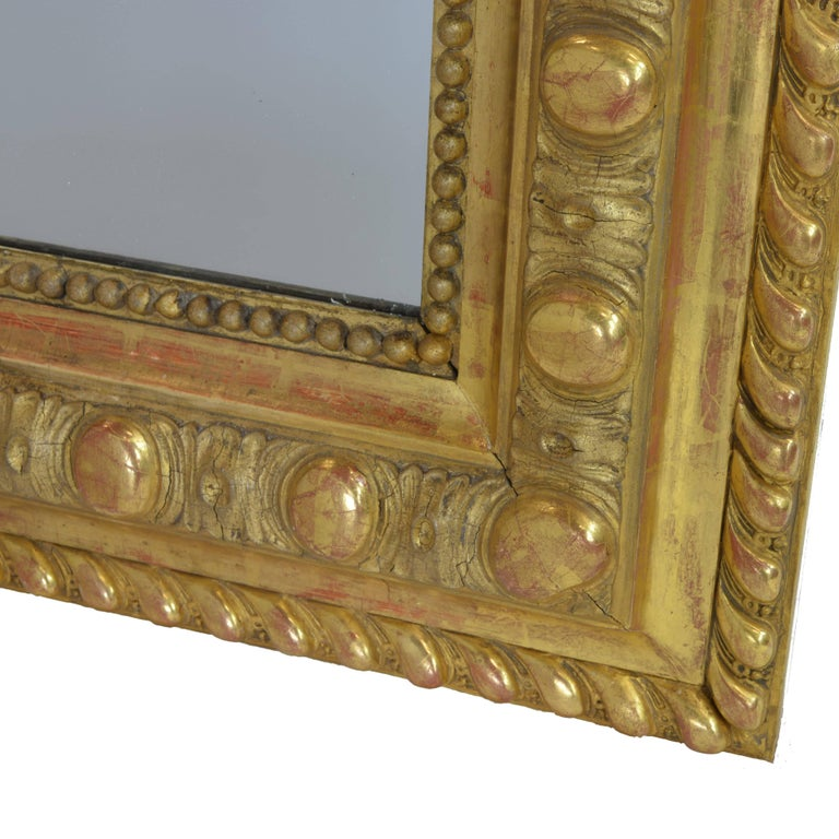 An extremely rare find. The artistic detail in the carved cherubs, floral garlands, and shield adorning the crown is such that it will hold any onlooker absolutely spellbound. The meticulously crafted, hand-carved wooden frame is gilded in