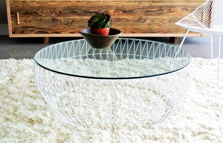 The coffee table by Bend Goods gives you all the surface space you could ever need for any living space.   The glass table top and patterned wire base, light easily passes through the table to keep an airy and minimalist feel. The round shape makes
