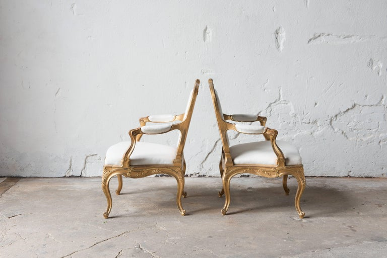 Pair of Swedish 19th century gilded armchairs. 1860s Rococo style. 
